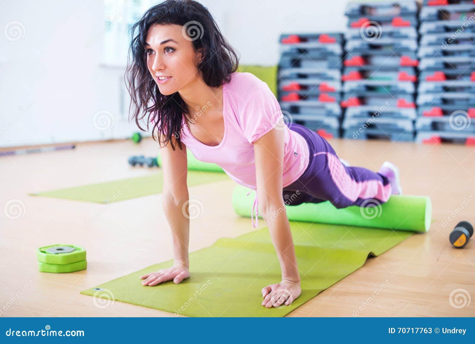 Dysponowany kobiety rozciąganie na podłogowym używa piankowym rolkowym robi deski ćwiczeniu, pcha podnosi