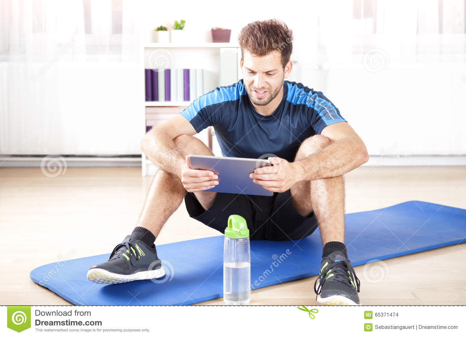 Dysponowany mężczyzna Używa jego pastylka komputer Po ćwiczenia