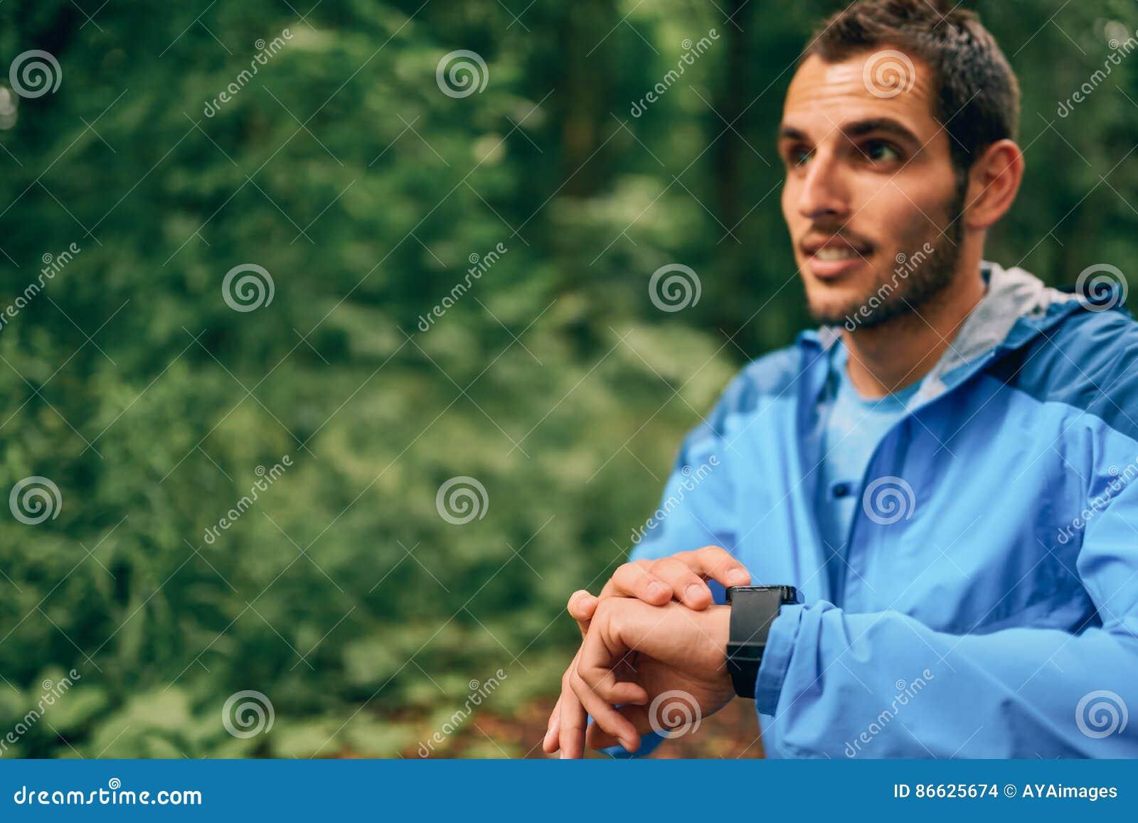 Dysponowany męski jogger dzień używać smartwatch podczas przecinającego kraju śladu lasowej rasy w natura parku