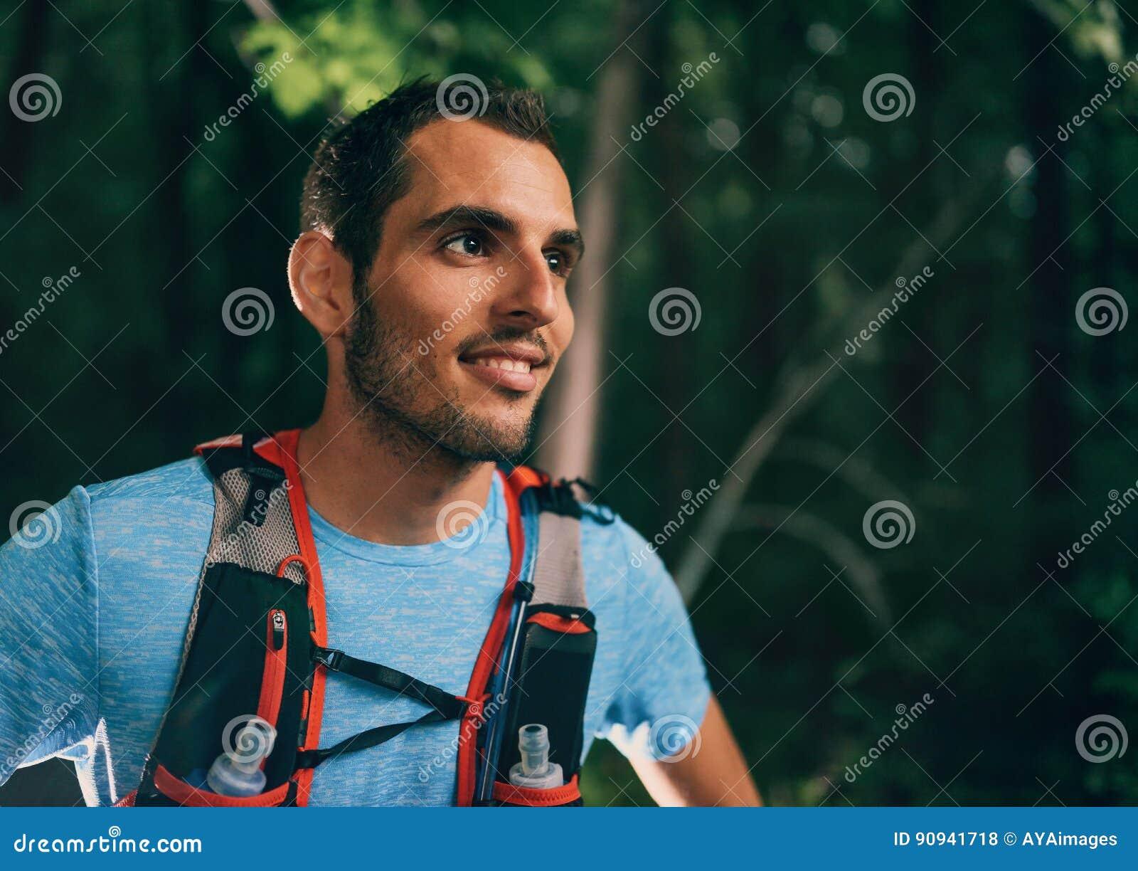 Dysponowany męski jogger odpoczywa podczas dnia szkolenia dla przecinającego kraju śladu lasowej rasy w natura parku