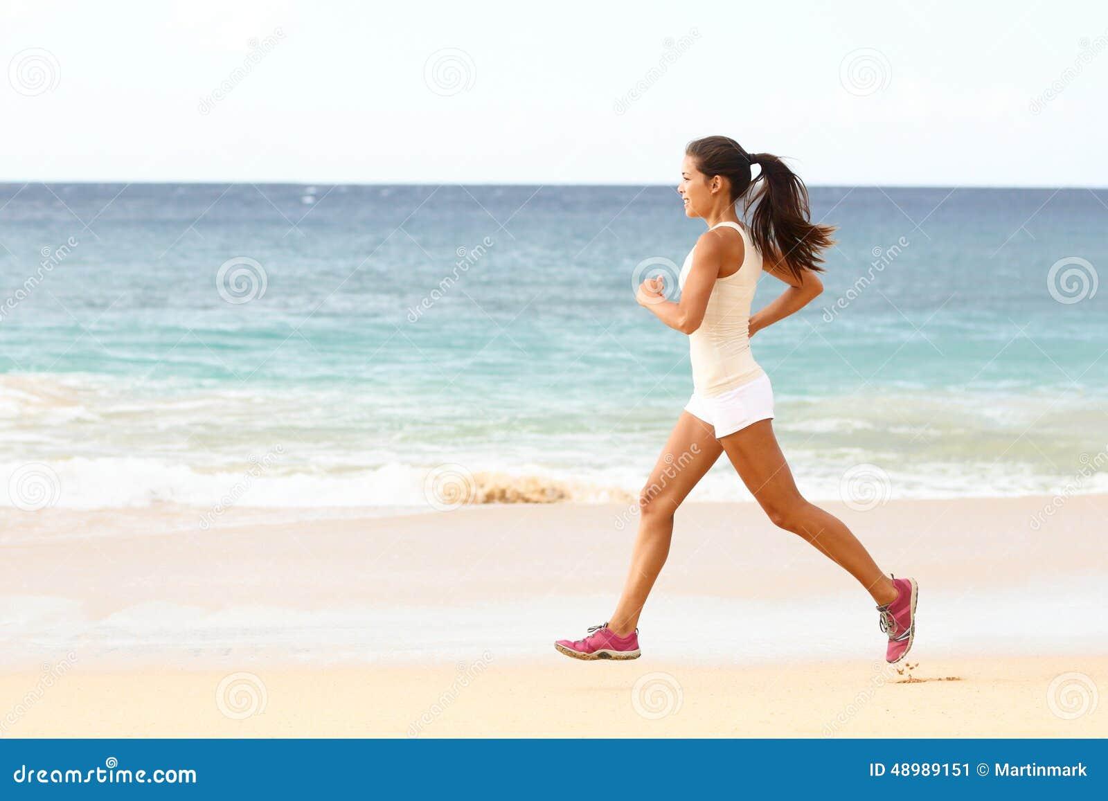 Dysponowany młoda kobieta bieg wzdłuż tropikalnej plaży