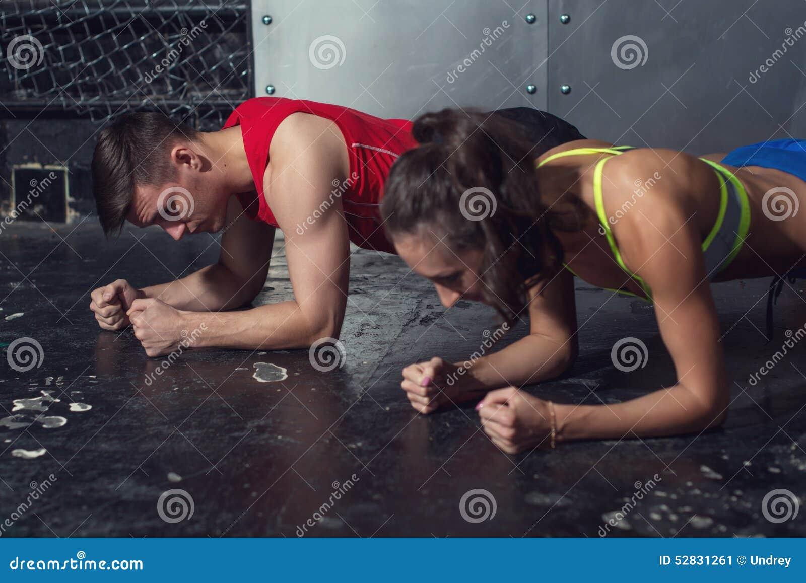 Dysponowany sportive mężczyzna i kobieta robi deski sedna