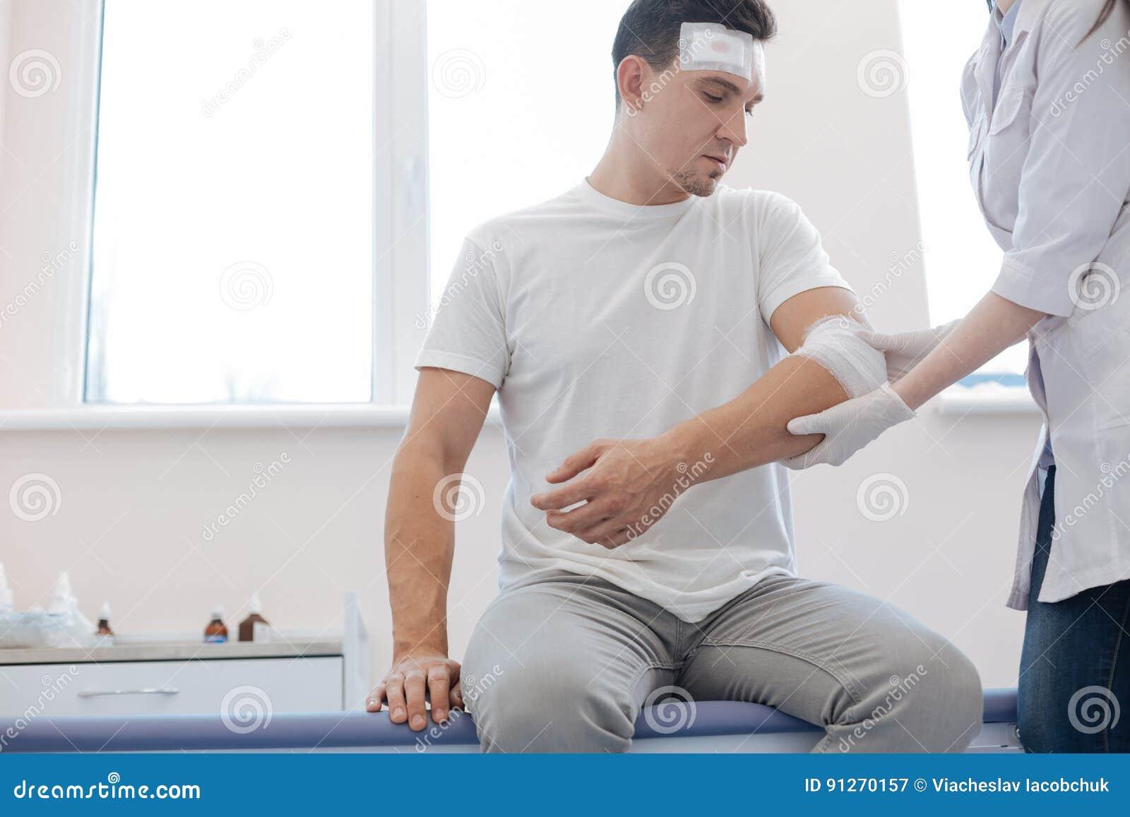 Dyster sårad man som ser hans skada