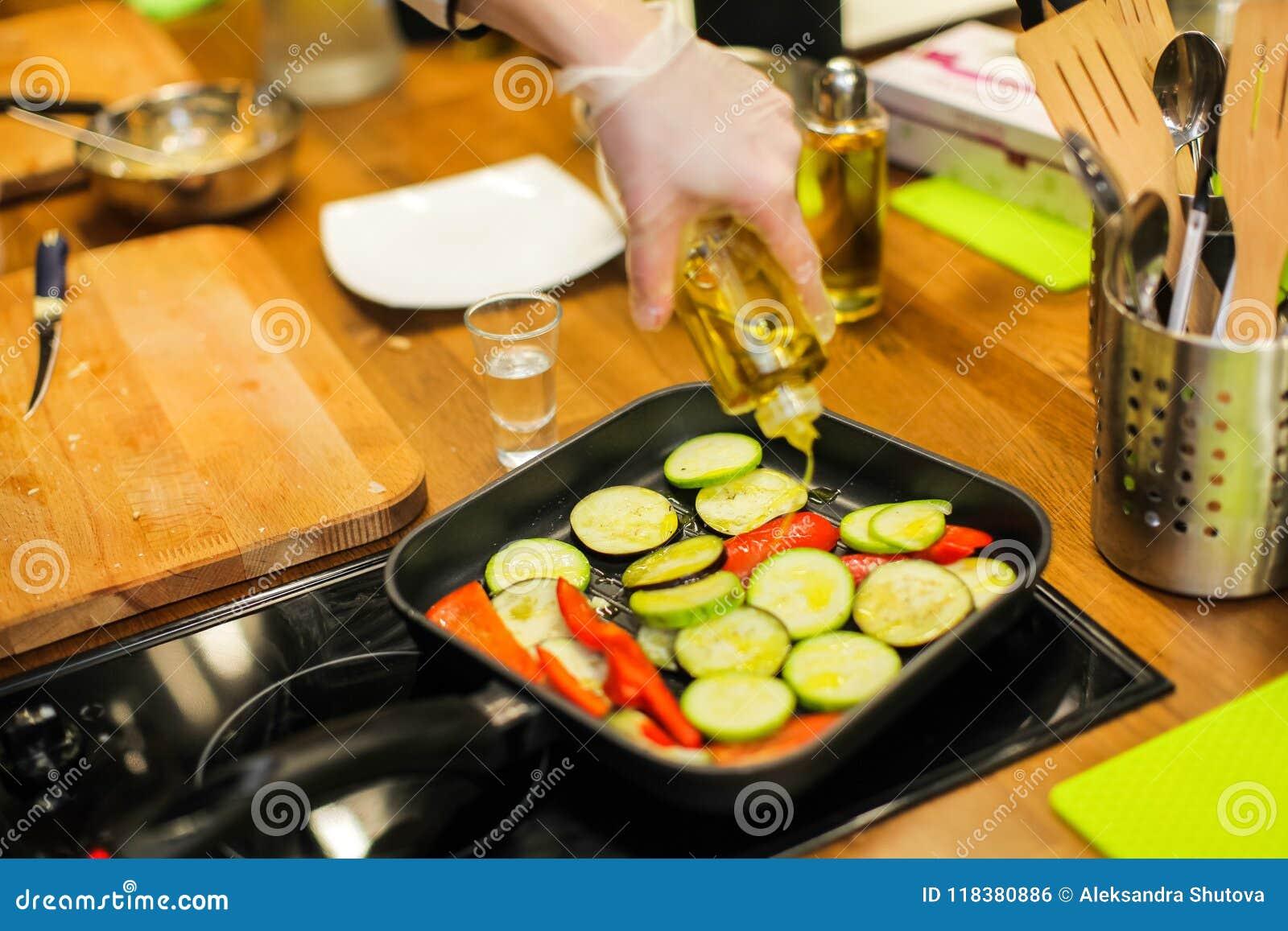 Dzbanek nalewa ciecz na niecce z warzywami Smażyć nieckę jest rozgrzewkowy up Potrzebuje niektóre oliwa z oliwek