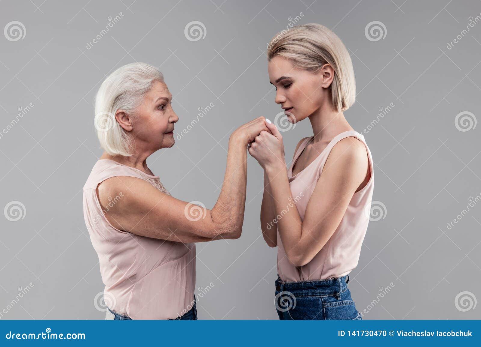 Dziękczynna blond dziewczyna z koczka ostrzyżenia oddychaniem na rękach jej senior matka