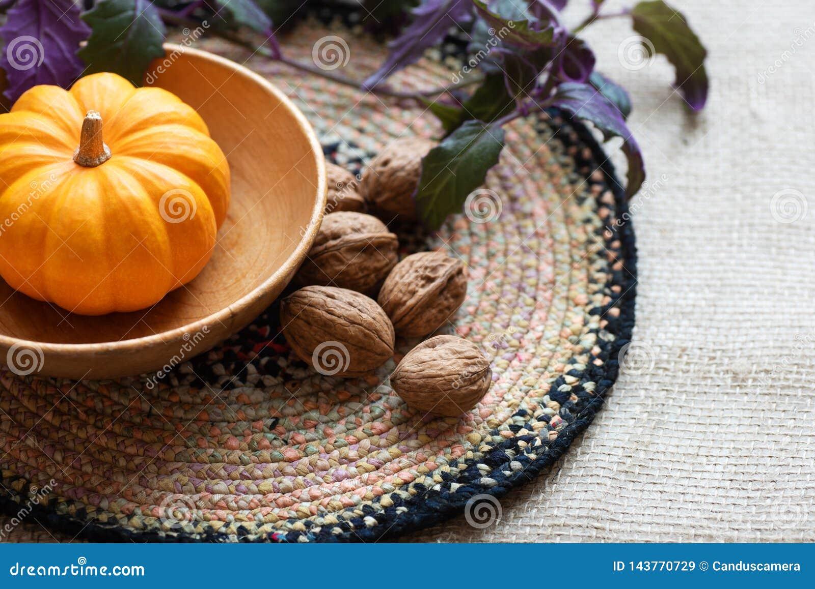 Dziękczynienie spadku Wciąż życie z Mini banią, orzechami włoskimi i rośliną jako centerpiece na stole z textured tkaniny tablecl