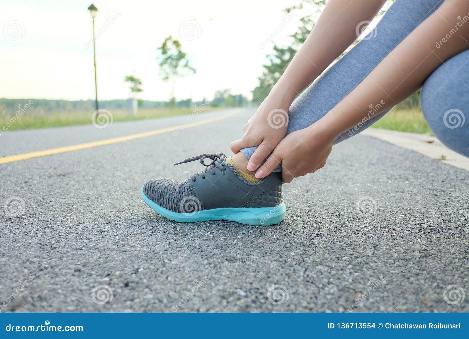Działający uraz nogi wypadku sporta kobiety biegacza kaleczenie trzyma bolesną zwichniętą kostkę w bólu