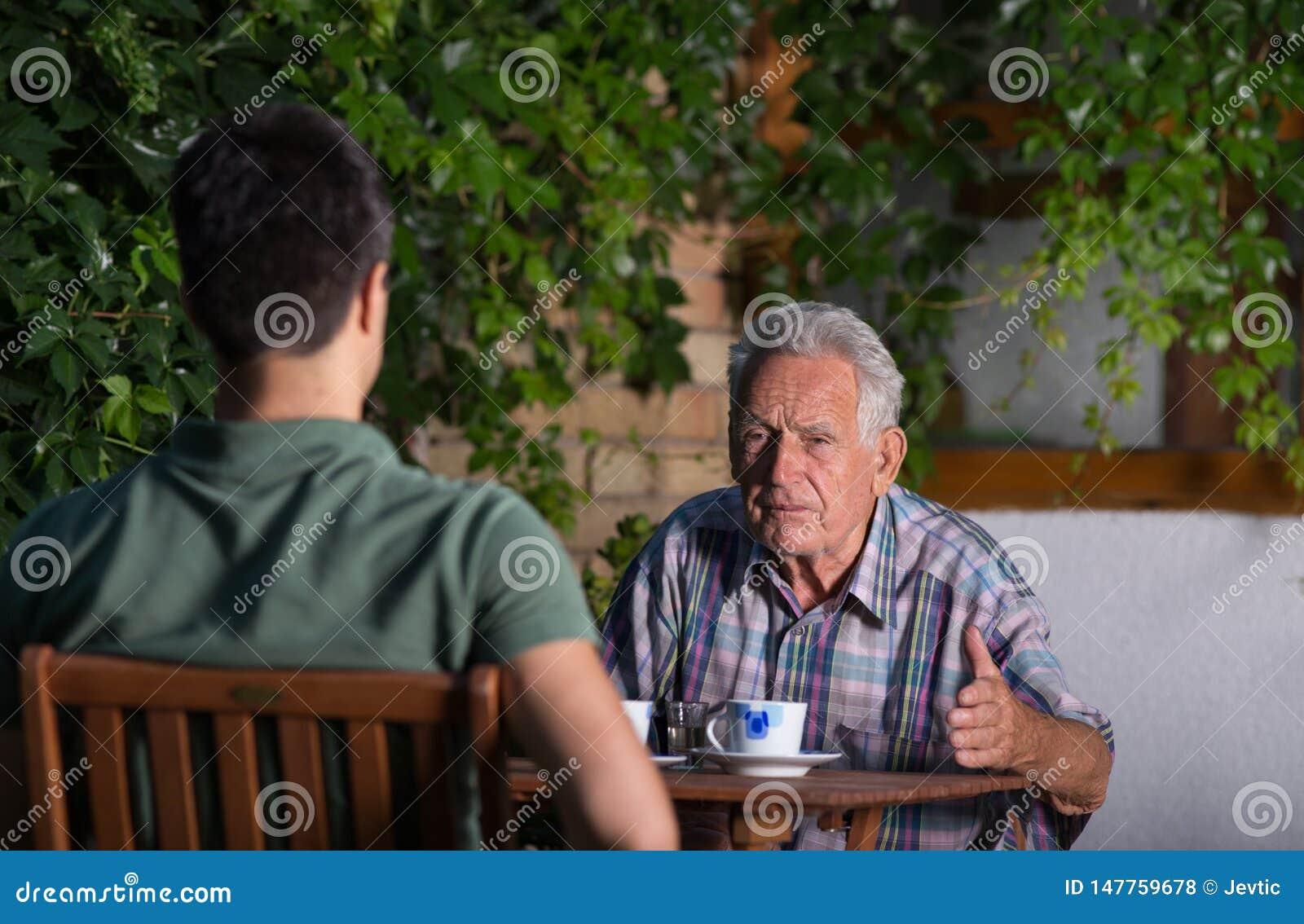 Dziad i wnuk opowiada w ogródzie