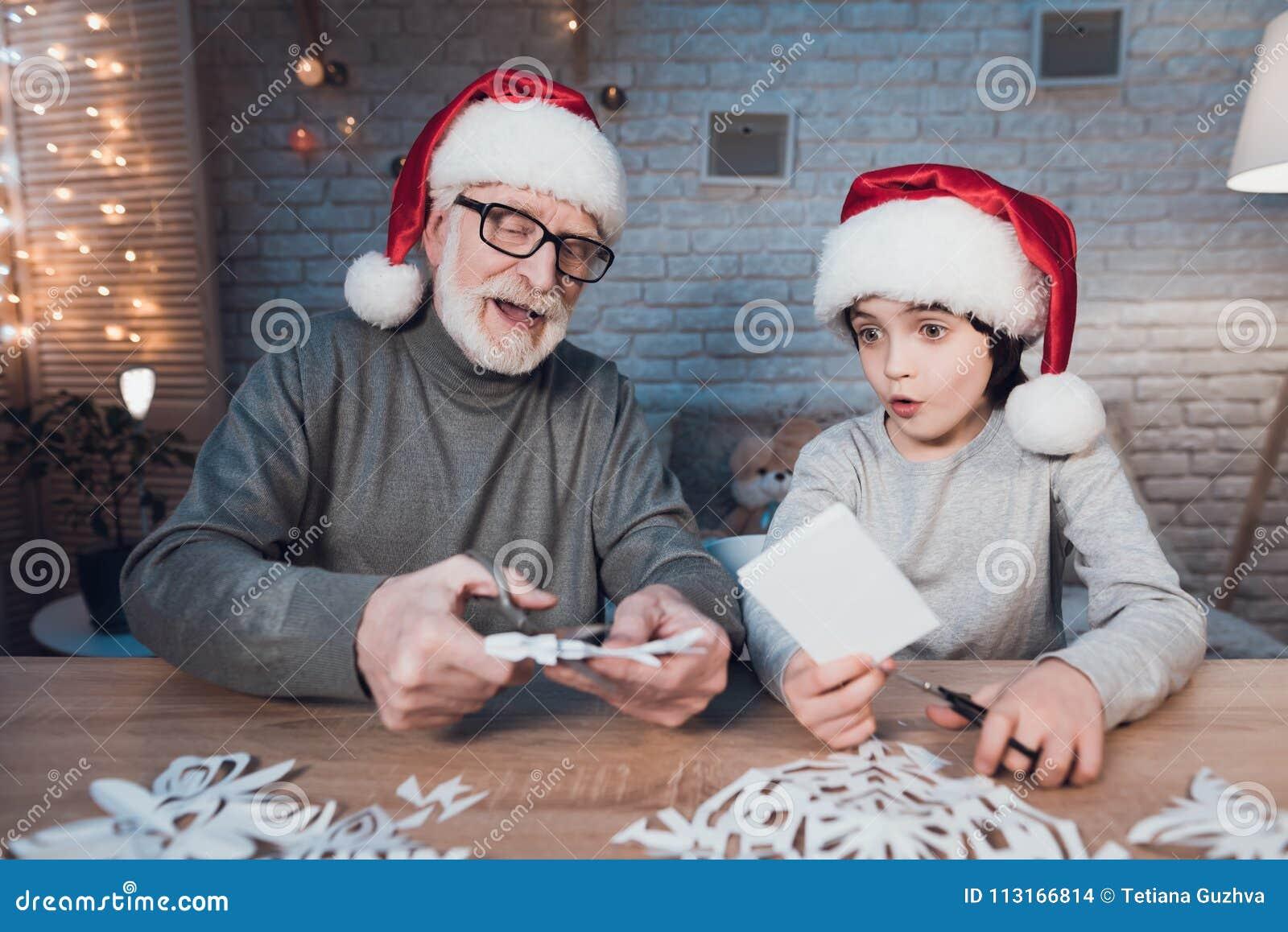 Dziad i wnuk robimy Bożenarodzeniowym dekoracjom przy nocą w domu