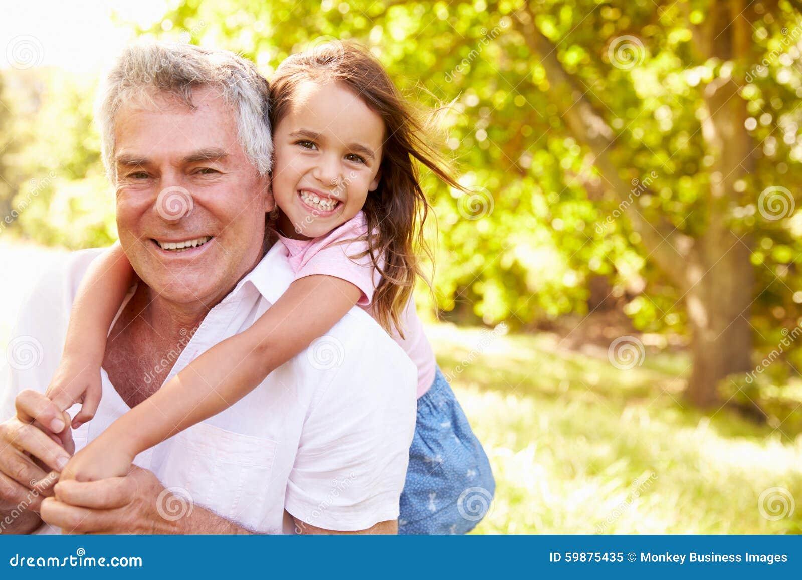 Dziad ma zabawę z jego wnuczką outdoors, portret