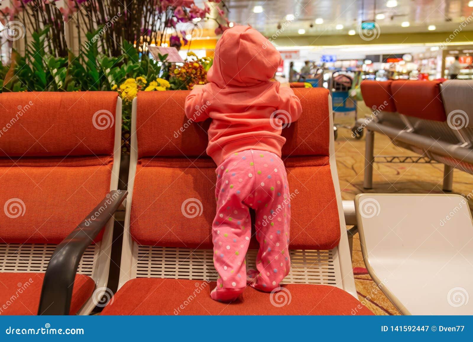 Dziecięce dziewczyn podróże Pierwszy czas przy lotniskiem Dziecko w żywej koralowej hoodie pozycji na krześle kamera, z powrotem