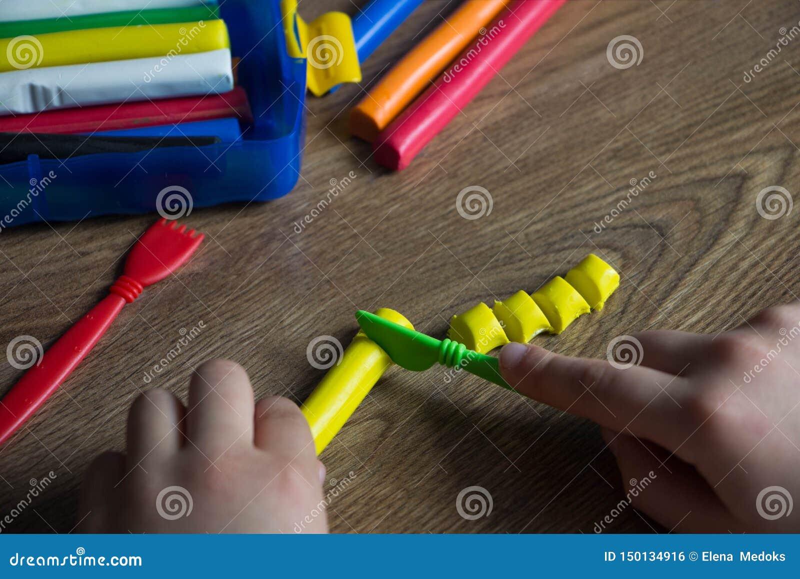 Dzieci bawią się w barwiącej plastelinie na drewnianym stole Kreatywnie z dziećmi