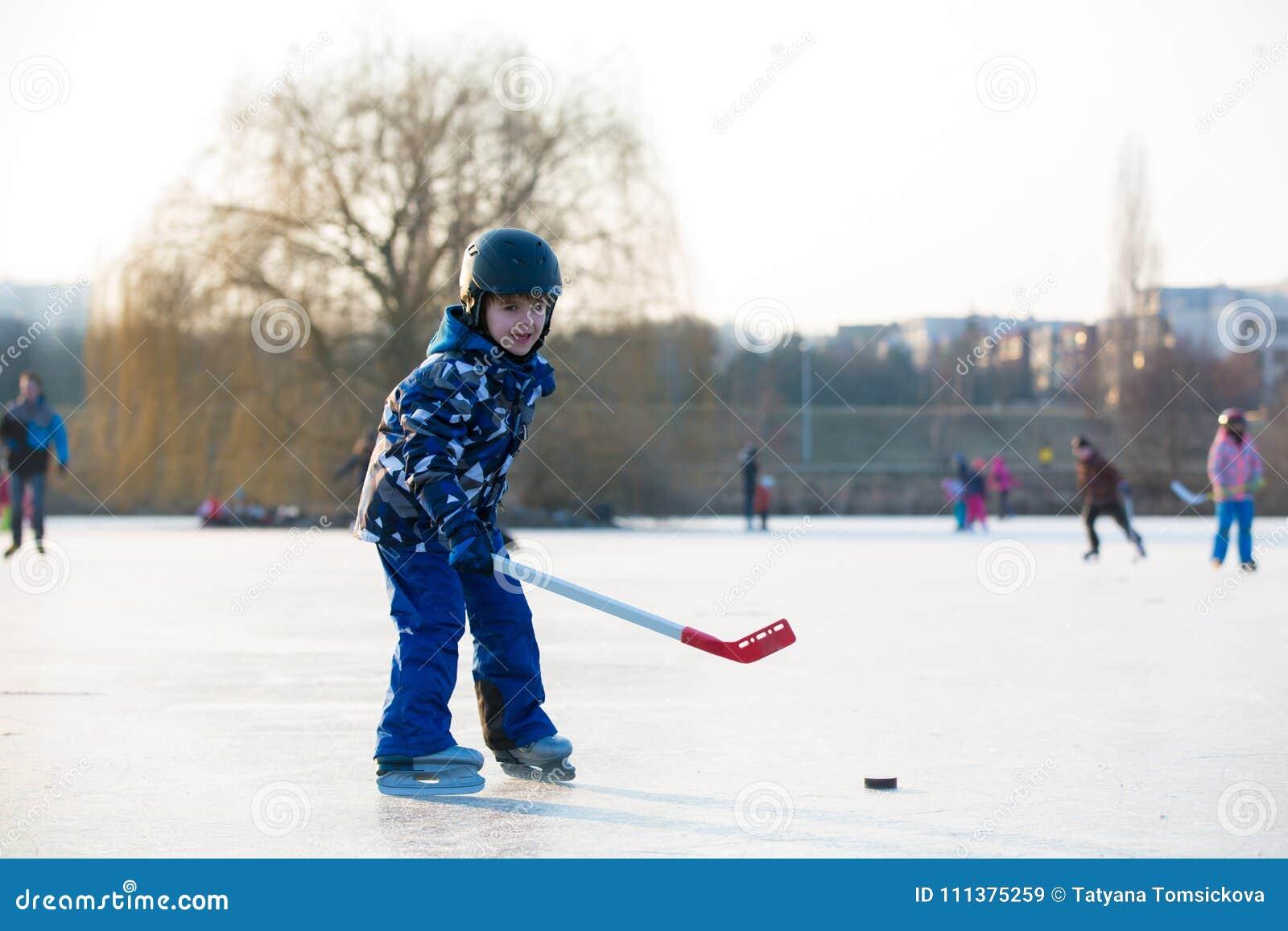 Dzieci, bawić się hokeja i łyżwiarstwo w parku na zamarzniętym jeziorze,