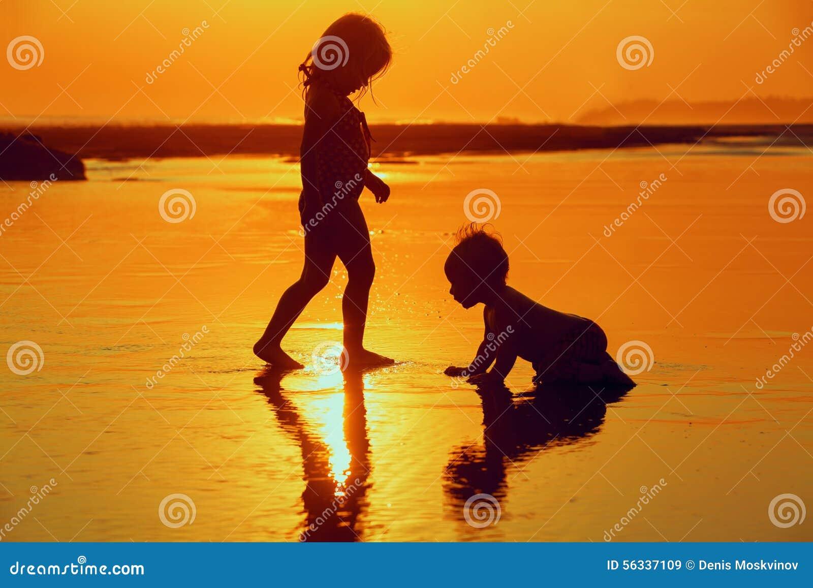 Dzieci bawić się z zabawą na zmierzchu morza plaży