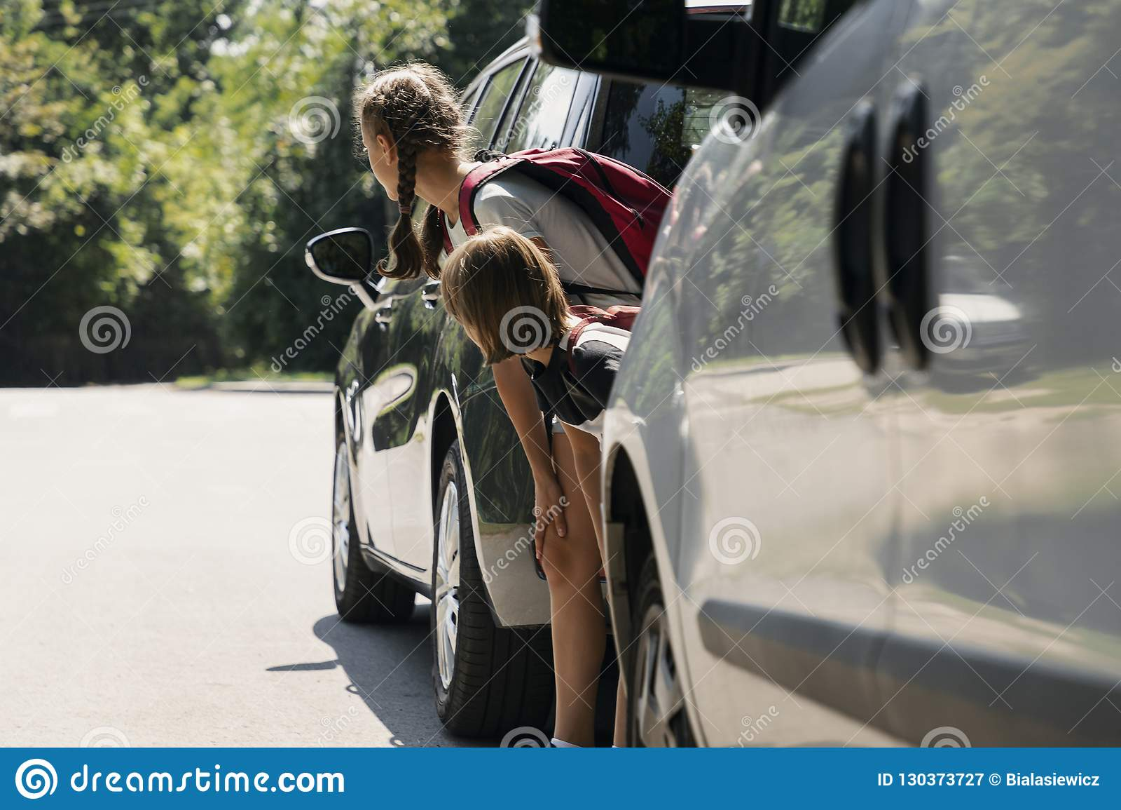Dzieci chodzi przez drogi między samochodami