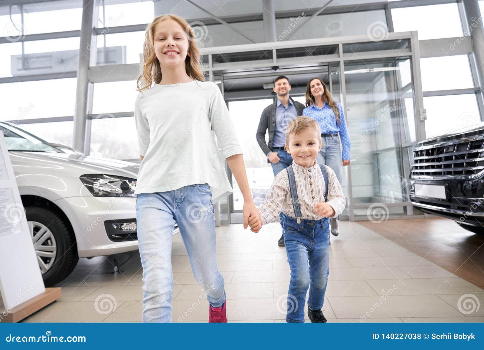 Dzieci i rodzice chodzi w samochodzie ześrodkowywają salę wystawową