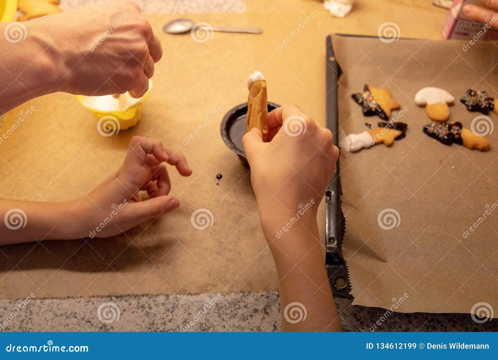 Dzieci kształtujący i tnący wypiekowi ciastka dla bożych narodzeń