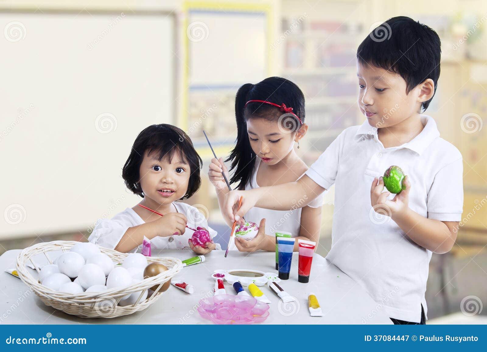 Download Dzieci maluje Easter jajka obraz stock. Obraz złożonej z jajka - 37084447