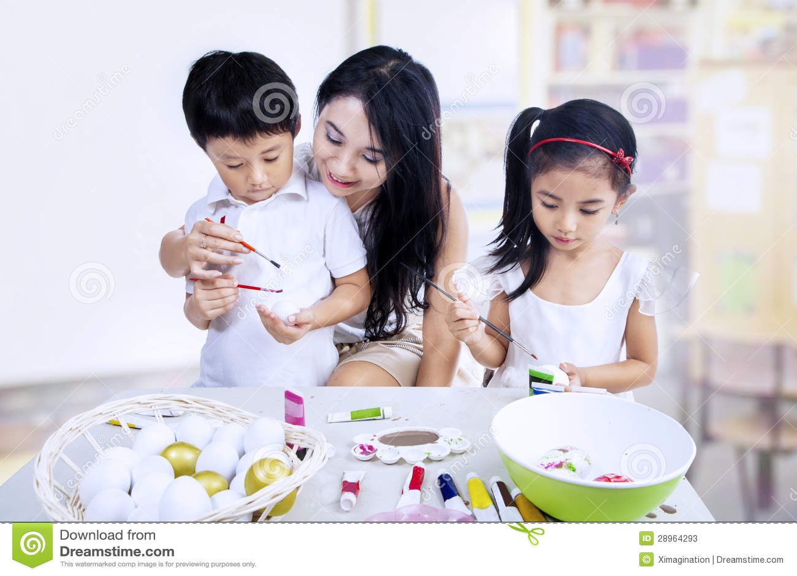 Dzieci maluje jajka w klasie