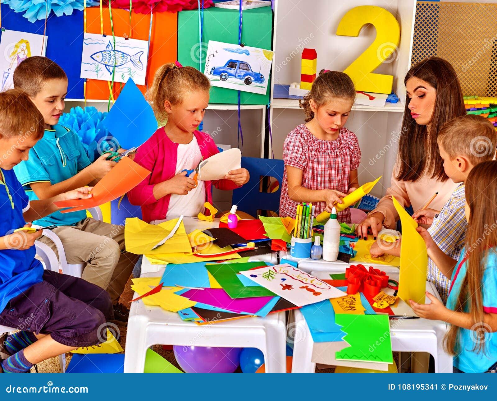 Dzieci robią coś z barwionego papieru