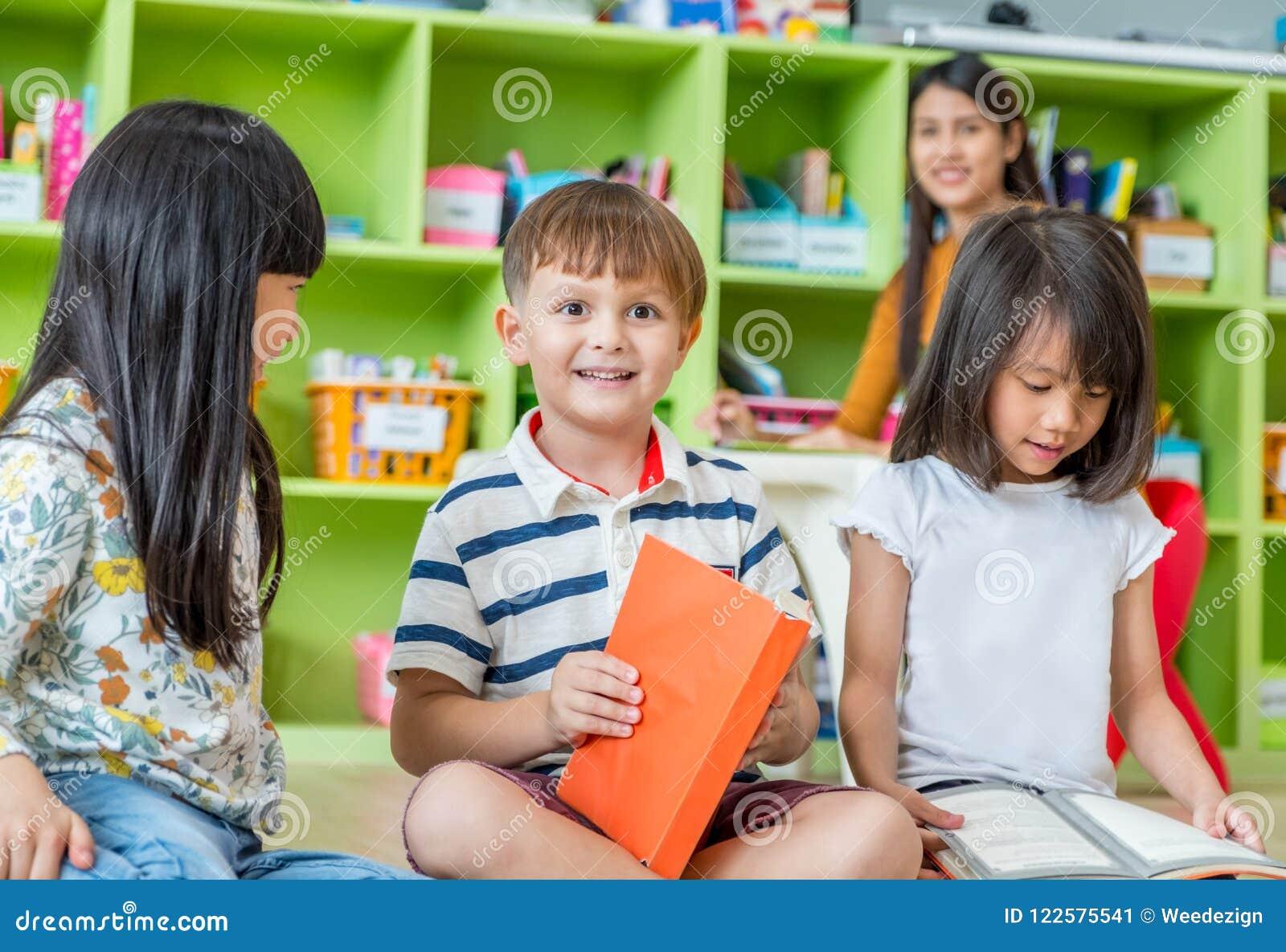 Dzieci siedzi na podłoga i czytelniczej bajce rezerwują w preschool li