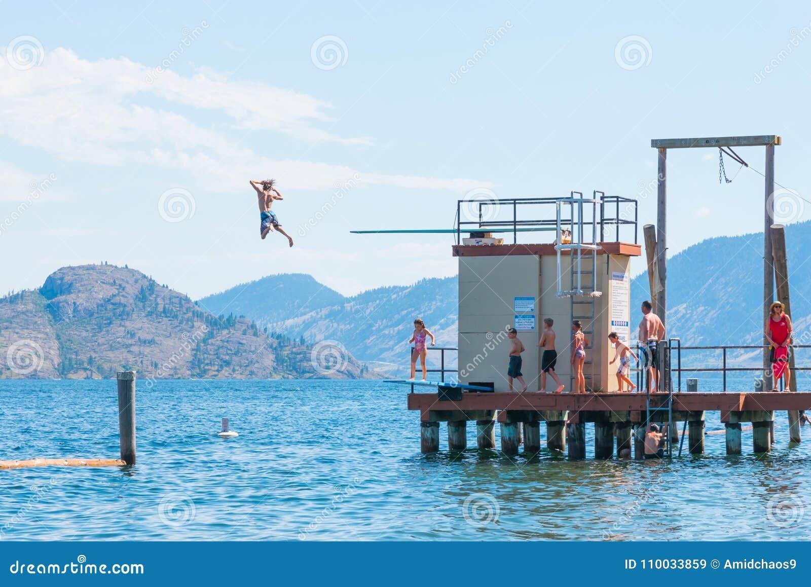 Dzieci skaczą z nurkowej deski w Okanagan jezioro przy pływanie zatoką