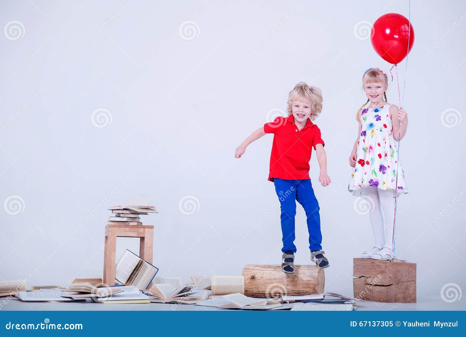 Dzieci z barwionymi balonami Fotografia wziąć w białym studiu Udział książki kłama na podłoga