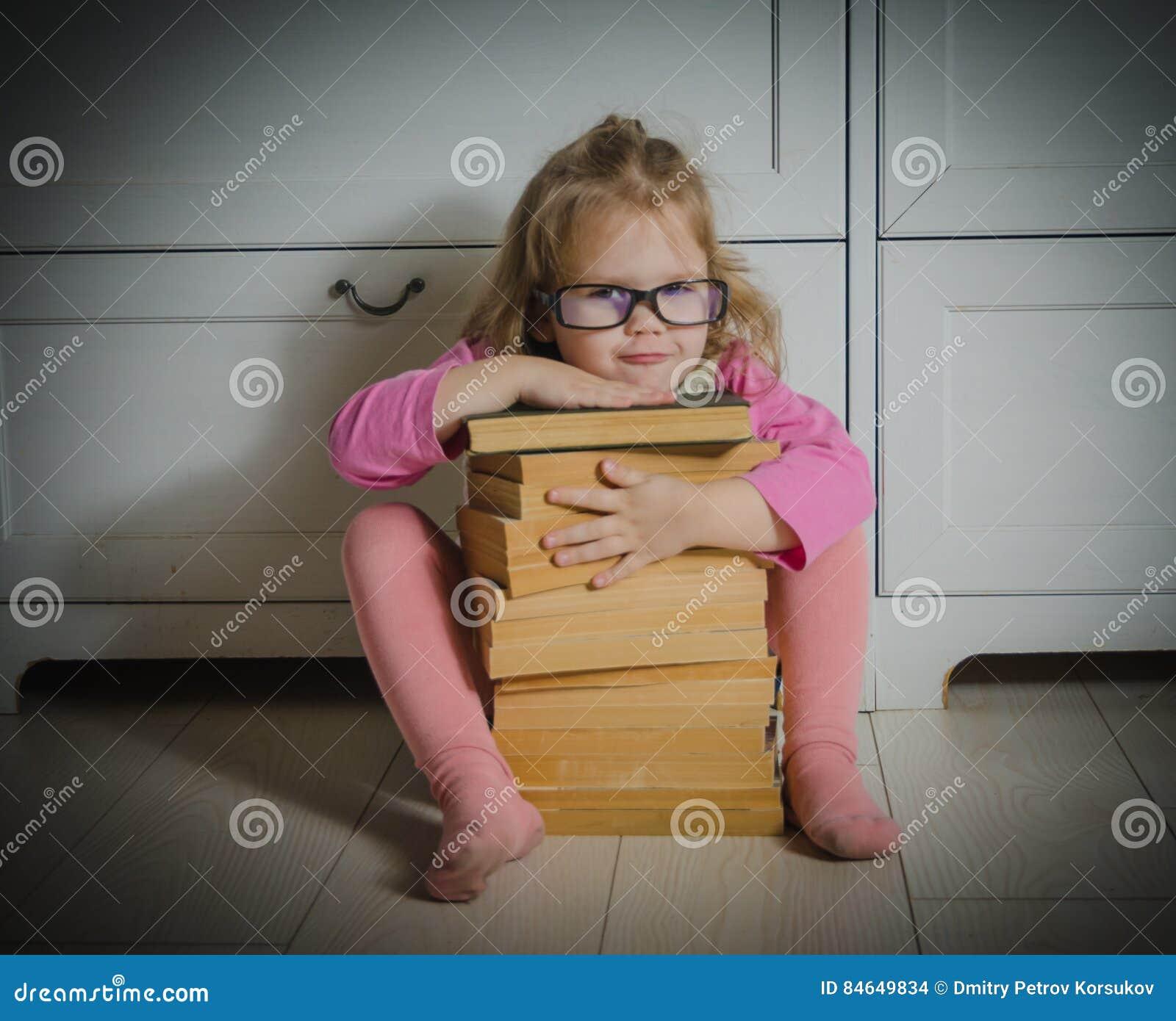 Dzieciak dziewczyna siedzi na podłoga z szkłami i sterta książki