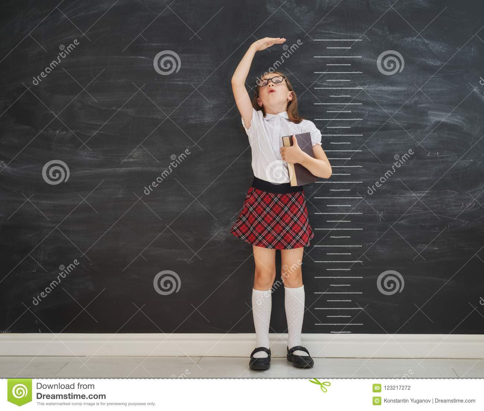 Dzieciak mierzy przyrosta na tle blackboard