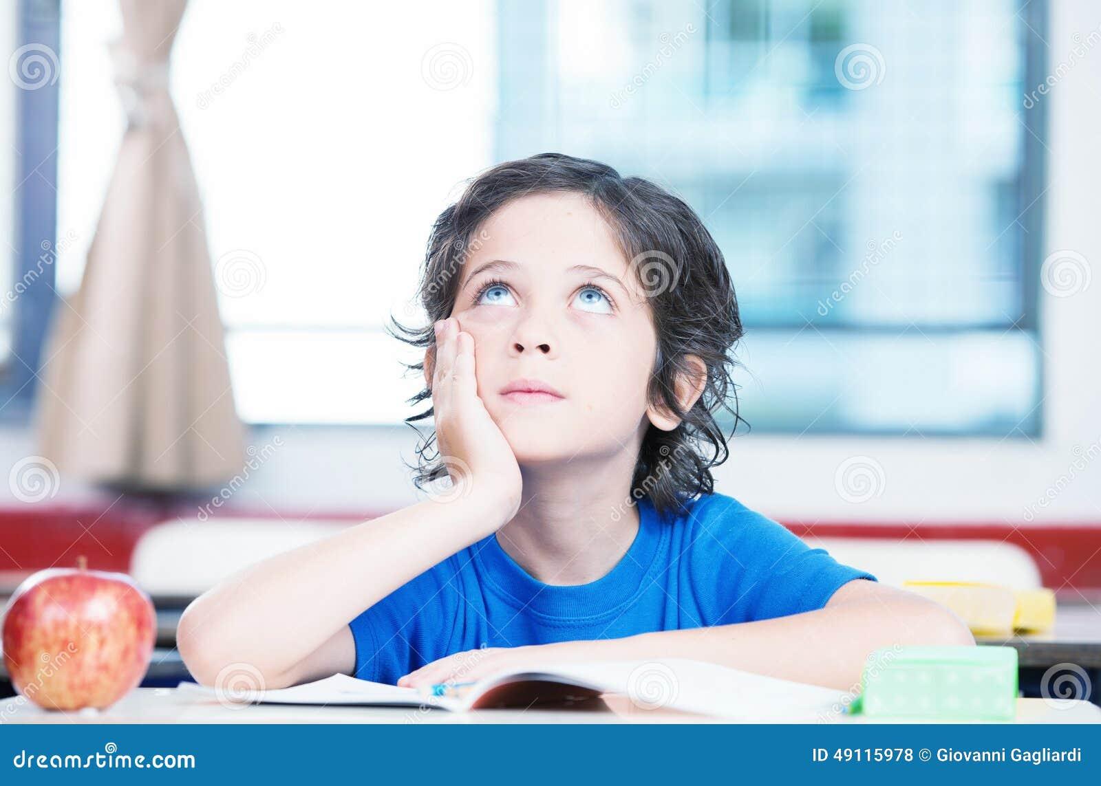 Dzieciak myśleć patrzeć oddolny przy szkolnym biurkiem