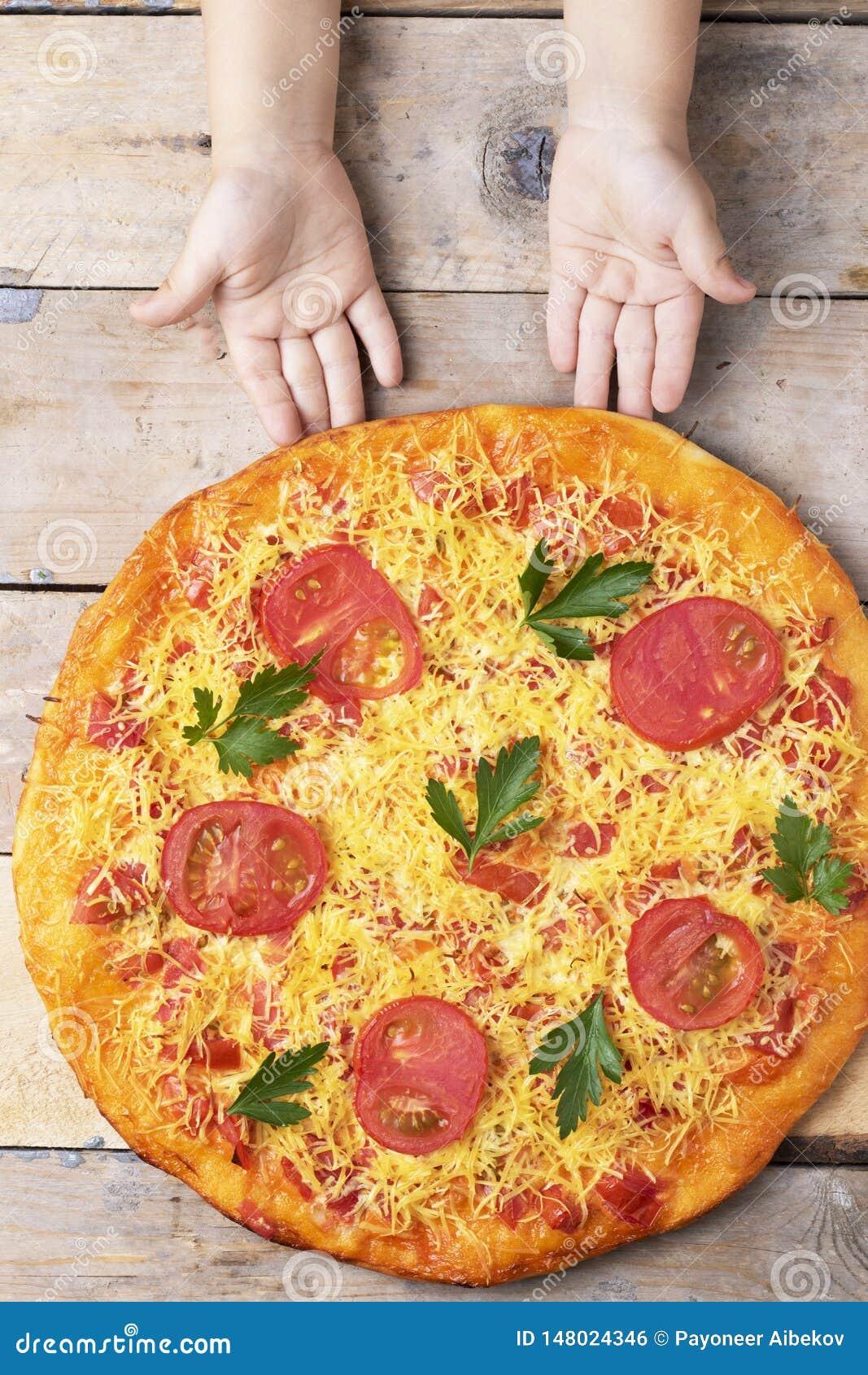 Dzieciak r?ki trzymaj? serow? pizz? z pomidorami i basilem, weganinu posi?ek na drewnianym wie?niaka stole, odg?rny widok