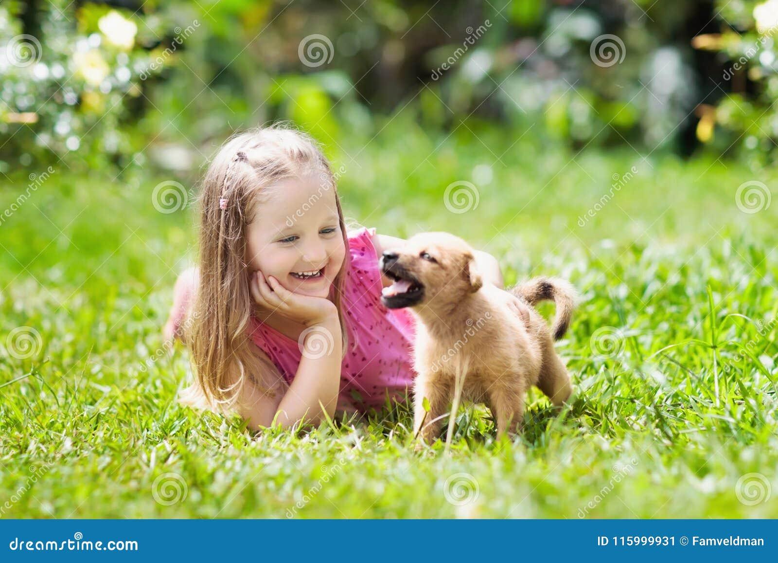 Dzieciak sztuka z szczeniakiem Dzieci i pies w ogródzie