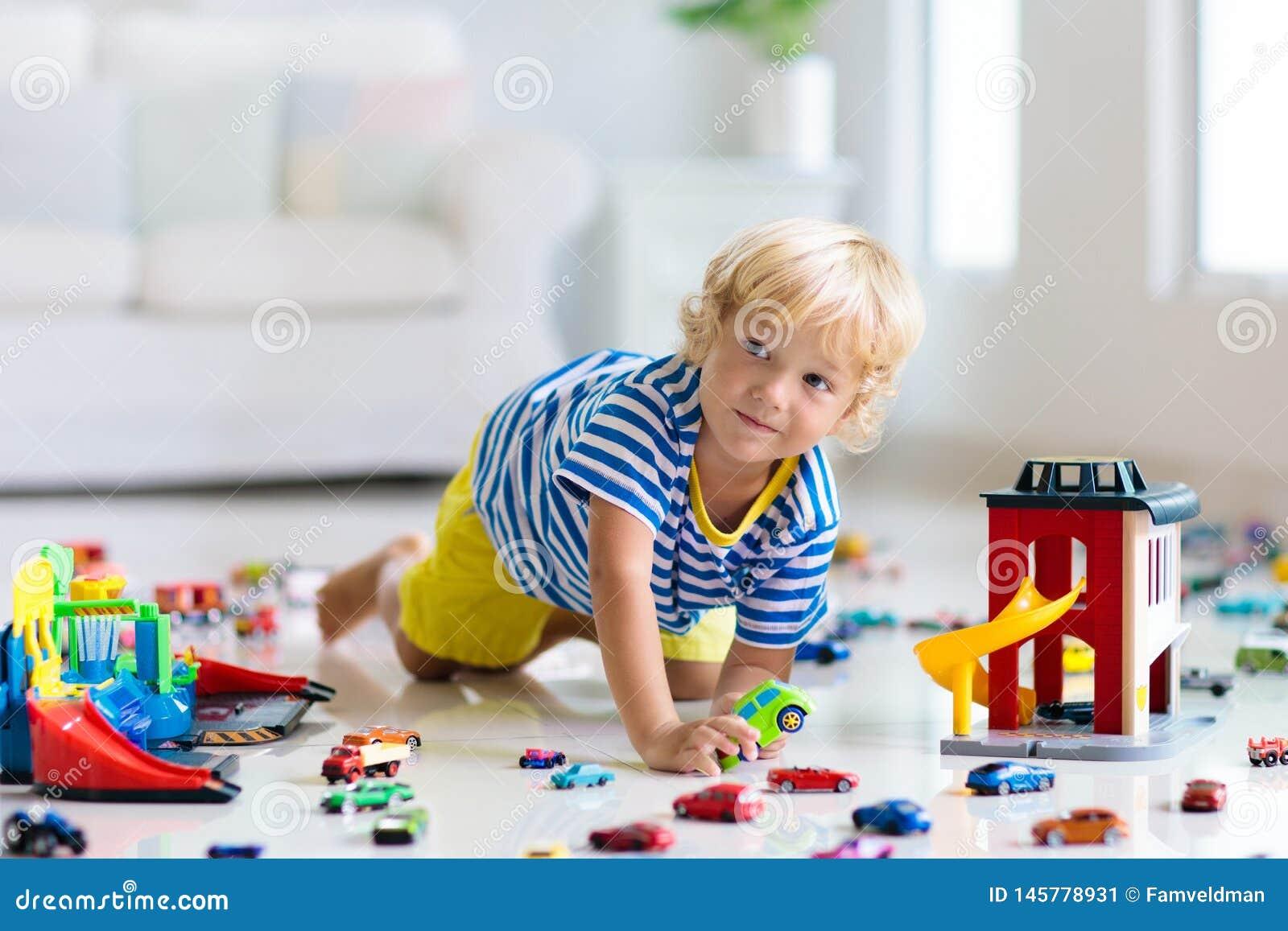 Dzieciak sztuka z zabawkarskimi samochodami Dzieci bawi? si? samoch?d zabawki