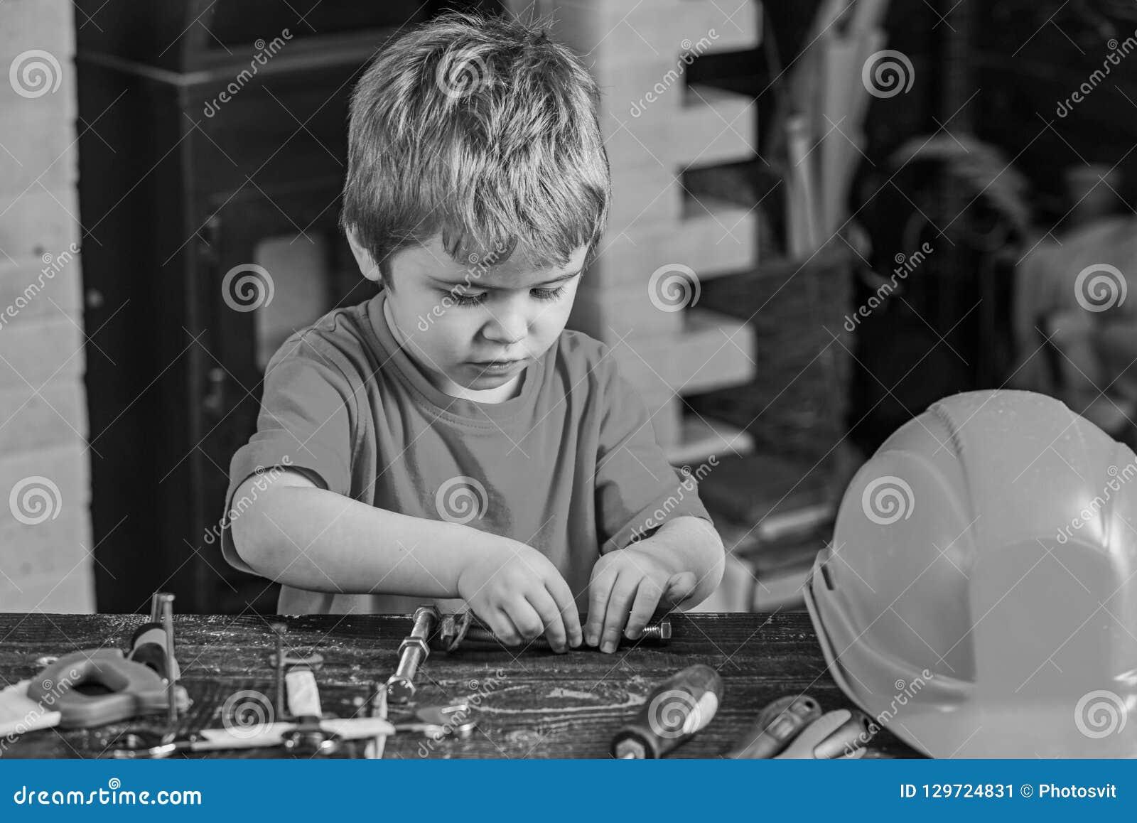 Dzieciak załatwia dwa metalu szczegółu Skoncentrowana chłopiec pracuje z śrubowymi ryglami Preschooler pomaga w warsztacie