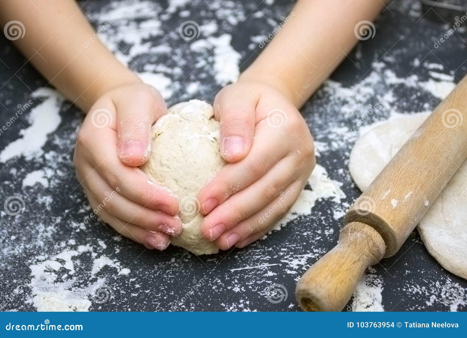 Dzieciaka ` s ręki, niektóre mąka, pszeniczny ciasto i toczna szpilka na czarnym stole, Dzieci wręczają robić żyta ciastu dla pop