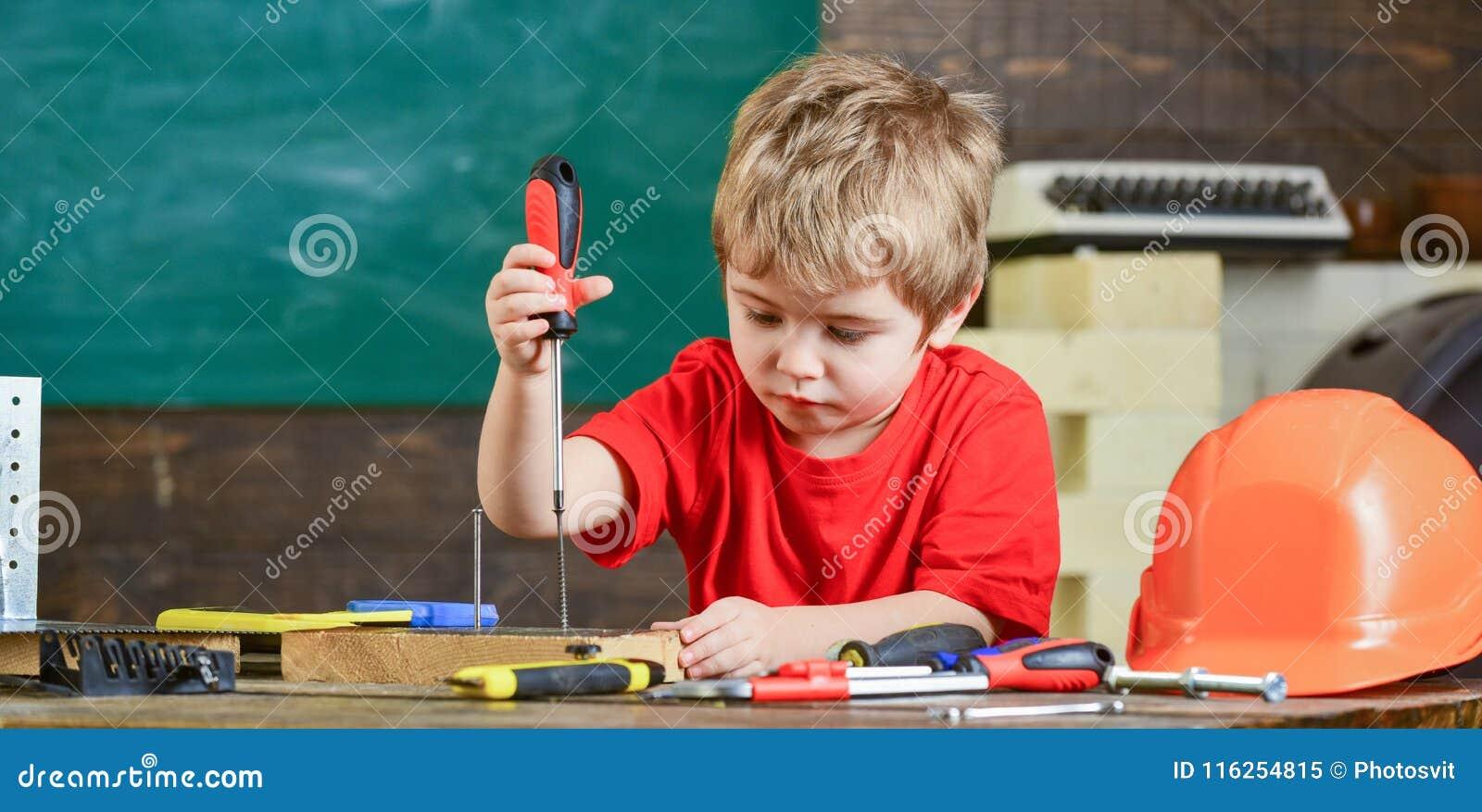 Dzieciaka uczenie używać śrubokręt Skoncentrowany dzieciak pracuje w naprawach warsztatowych Przyszłościowy zajęcia pojęcie