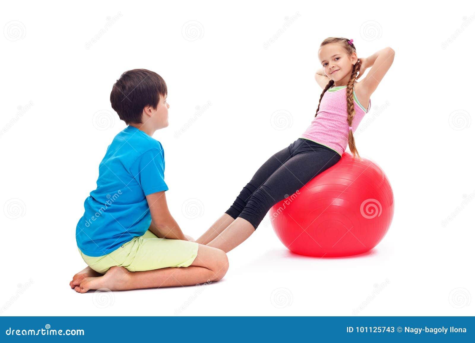 Dzieciaki ćwiczy wpólnie używać wielką gimnastyczną gumową piłkę