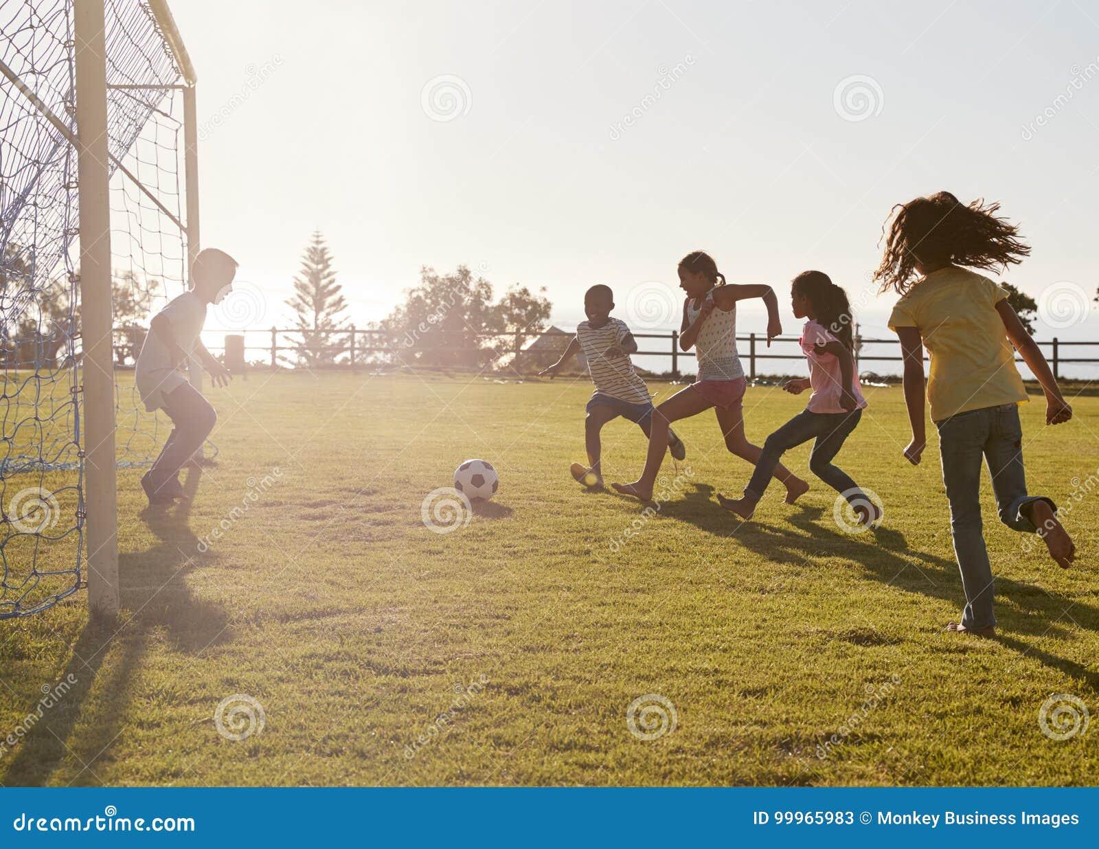 Dzieciaki bawić się futbol w parku, jeden w celu, boczny widok