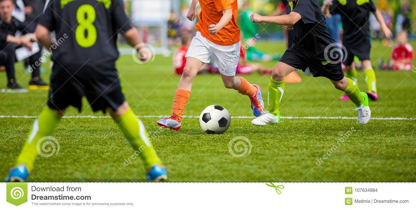 Dzieciaki bawić się futbolowego mecz piłkarskiego na sporta polu Chłopiec sztuki mecz piłkarski na Zielonej trawie Młodości piłki
