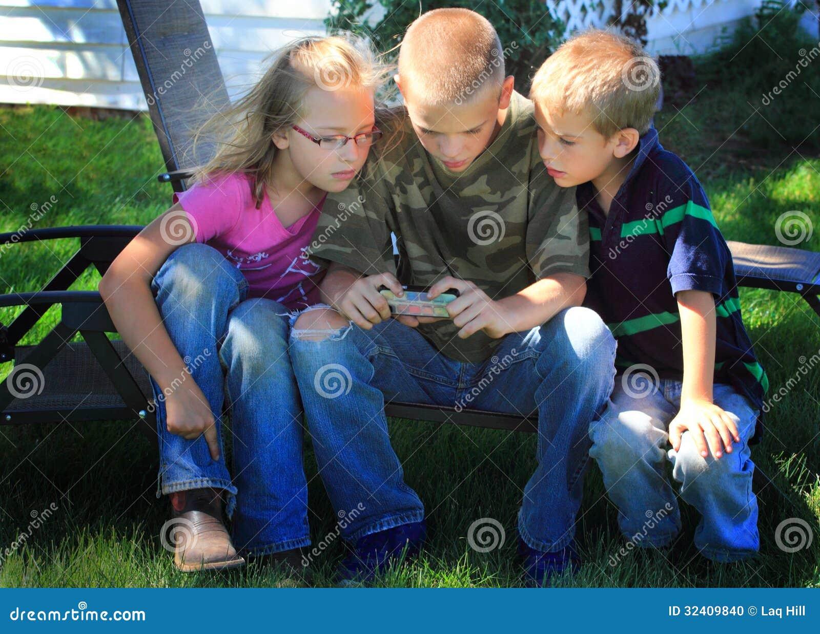 Dzieciaki bawić się na telefonie komórkowym