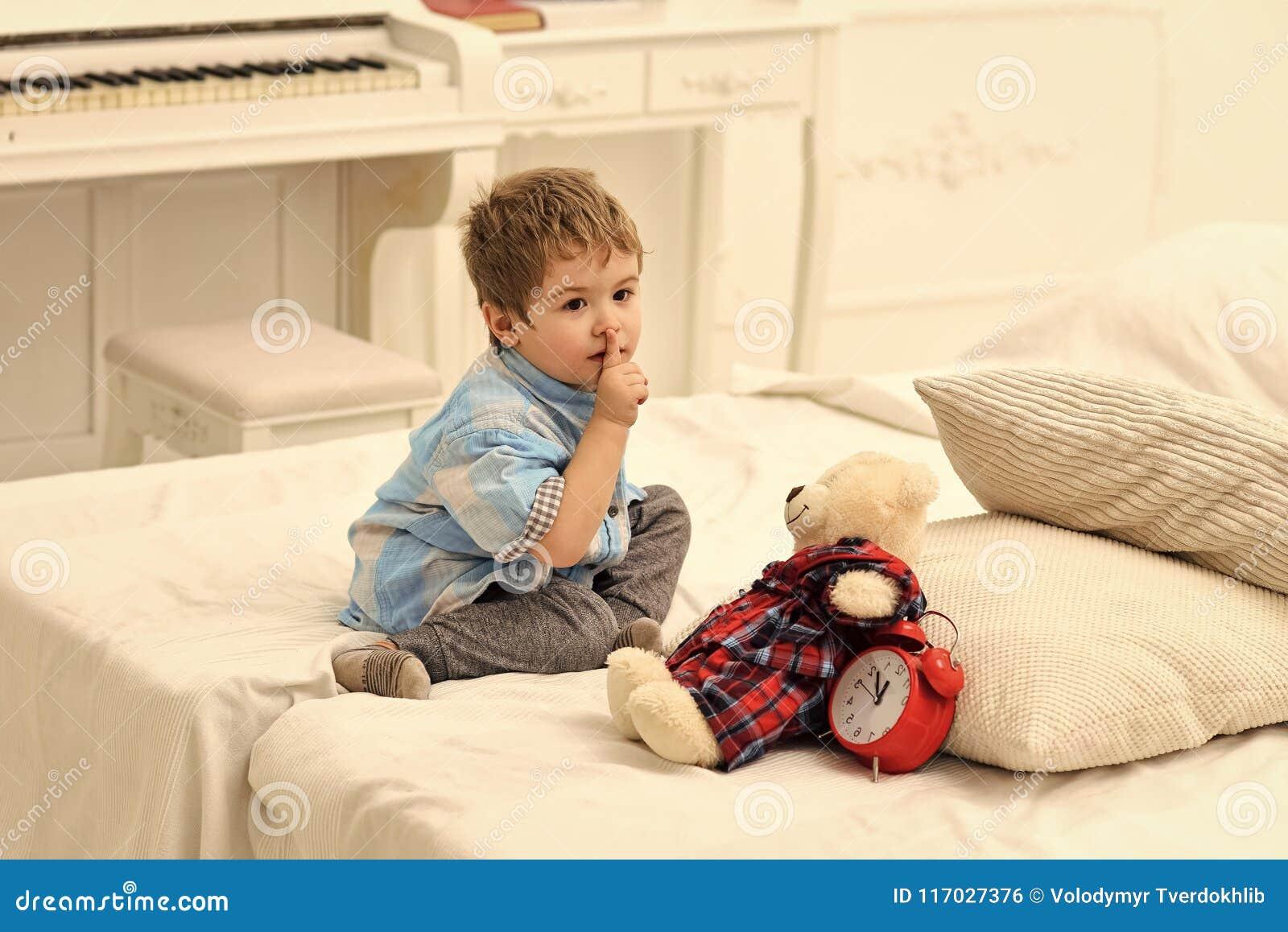 Dzieciaki bawić się zabawki Dziecko w sypialni z cisza gestem Dzieciak stawia mokiet niedźwiadkowe pobliskie poduszki i budzika,