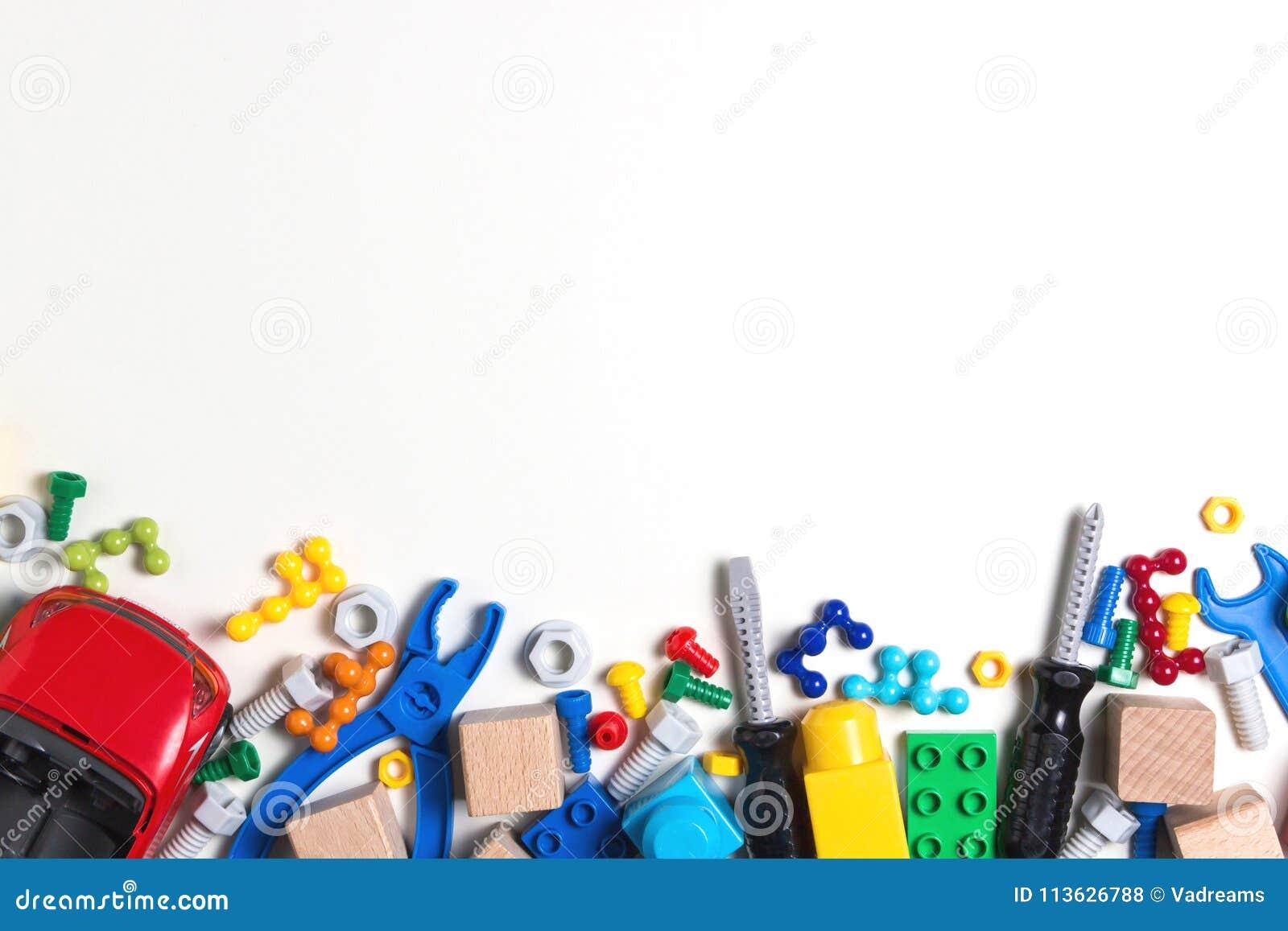 Dzieciaki bawją się tło z kolorowymi zabawkarskimi narzędziami, rygle, dokrętki, samochód, budowa bloki, sześciany na białym tle