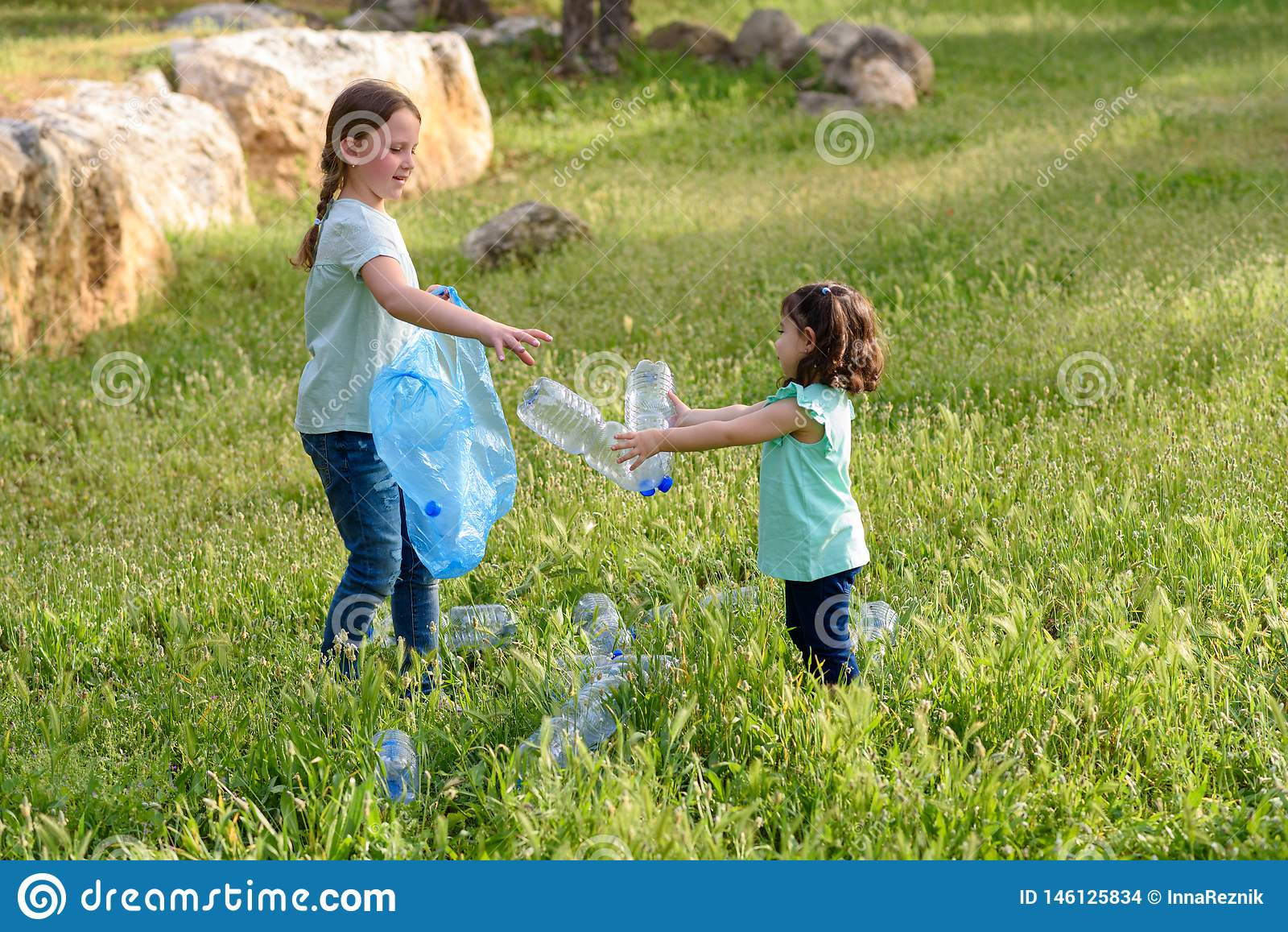 Dzieciaki czy?ci w parku Ochotniczy dzieci z torb? na ?miecie czy?ci w g?r? ?ci??ki, stawia plastikow? butelk? w przetwarza? torb