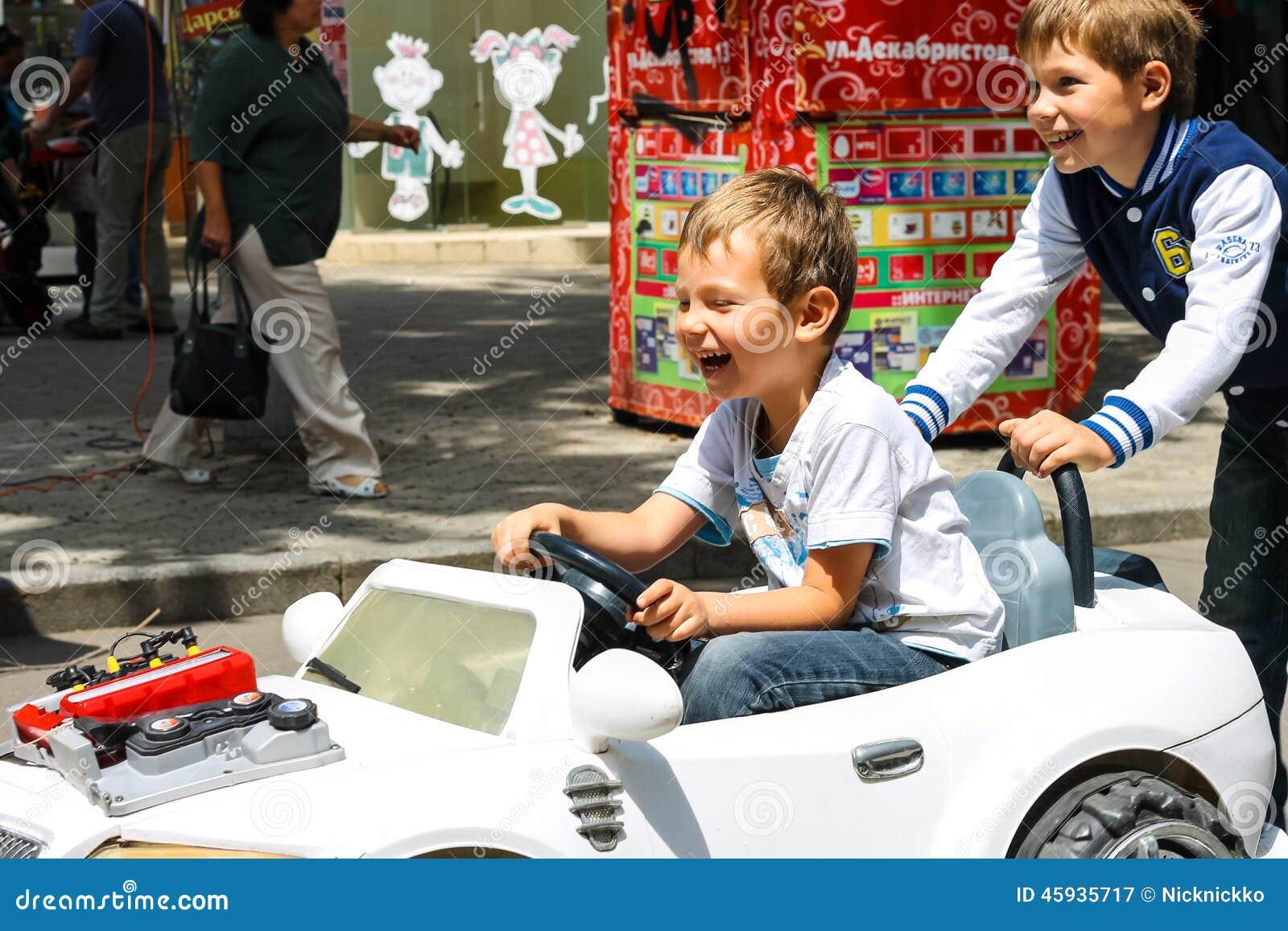 Dzieciaki jedzie zabawkarskiego samochód w sztuka terenie Nikolaev, Ukraina