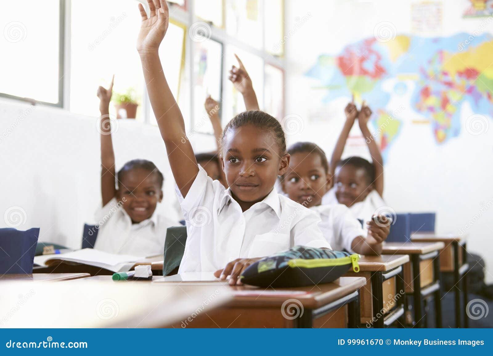 Dzieciaki podnosi ręki podczas lekci przy szkołą podstawową