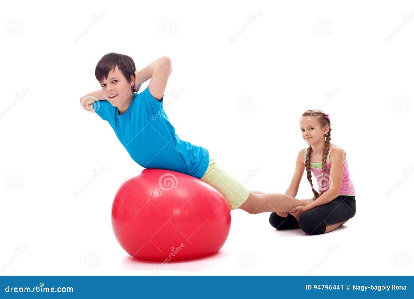 Dzieciaki pomaga each inny ćwiczy z wielką gimnastyczną gumą