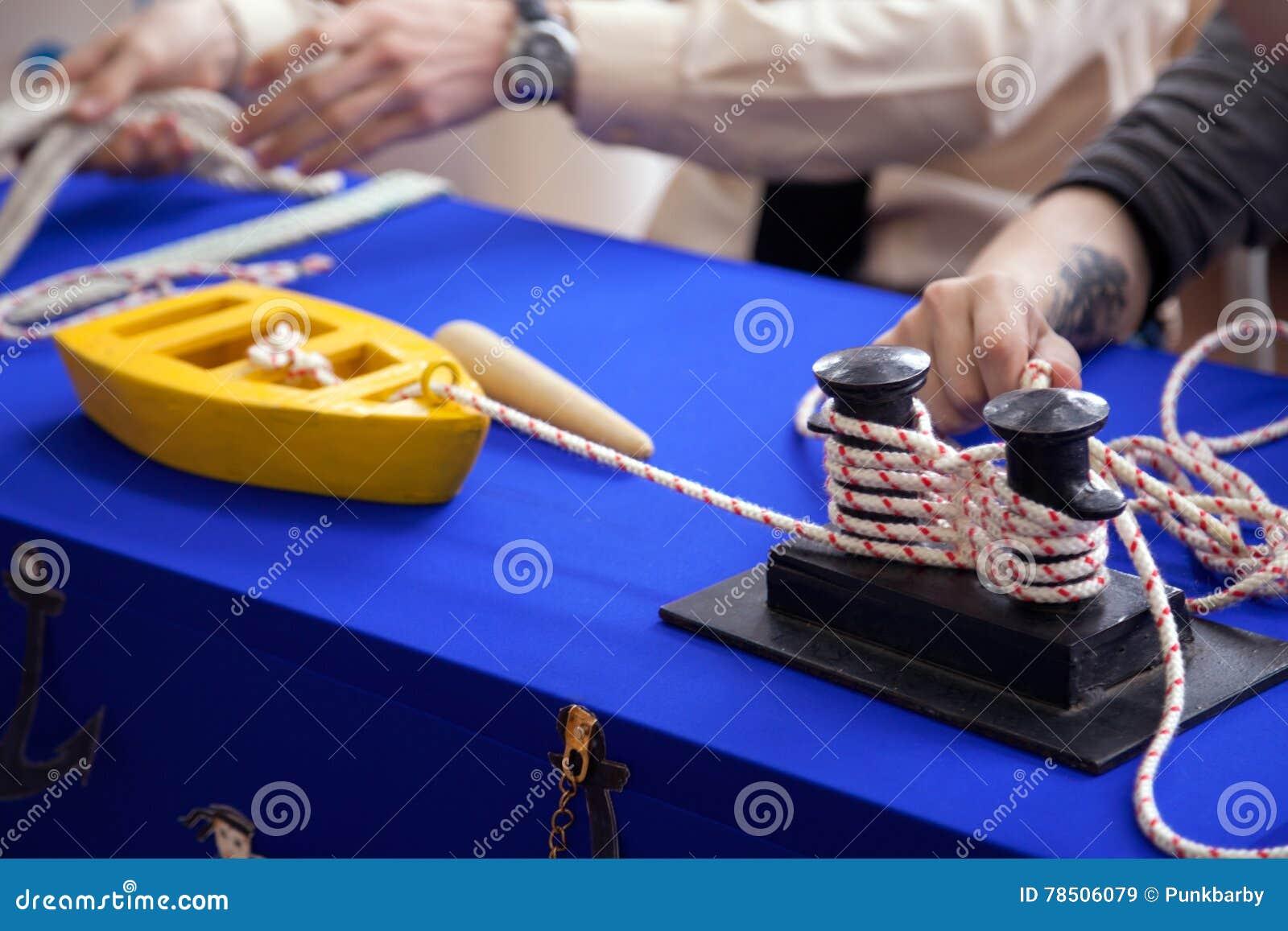 Dzieciaki uczy się cumować na zabawkarskim statku modelu przy żeglowanie szkołą