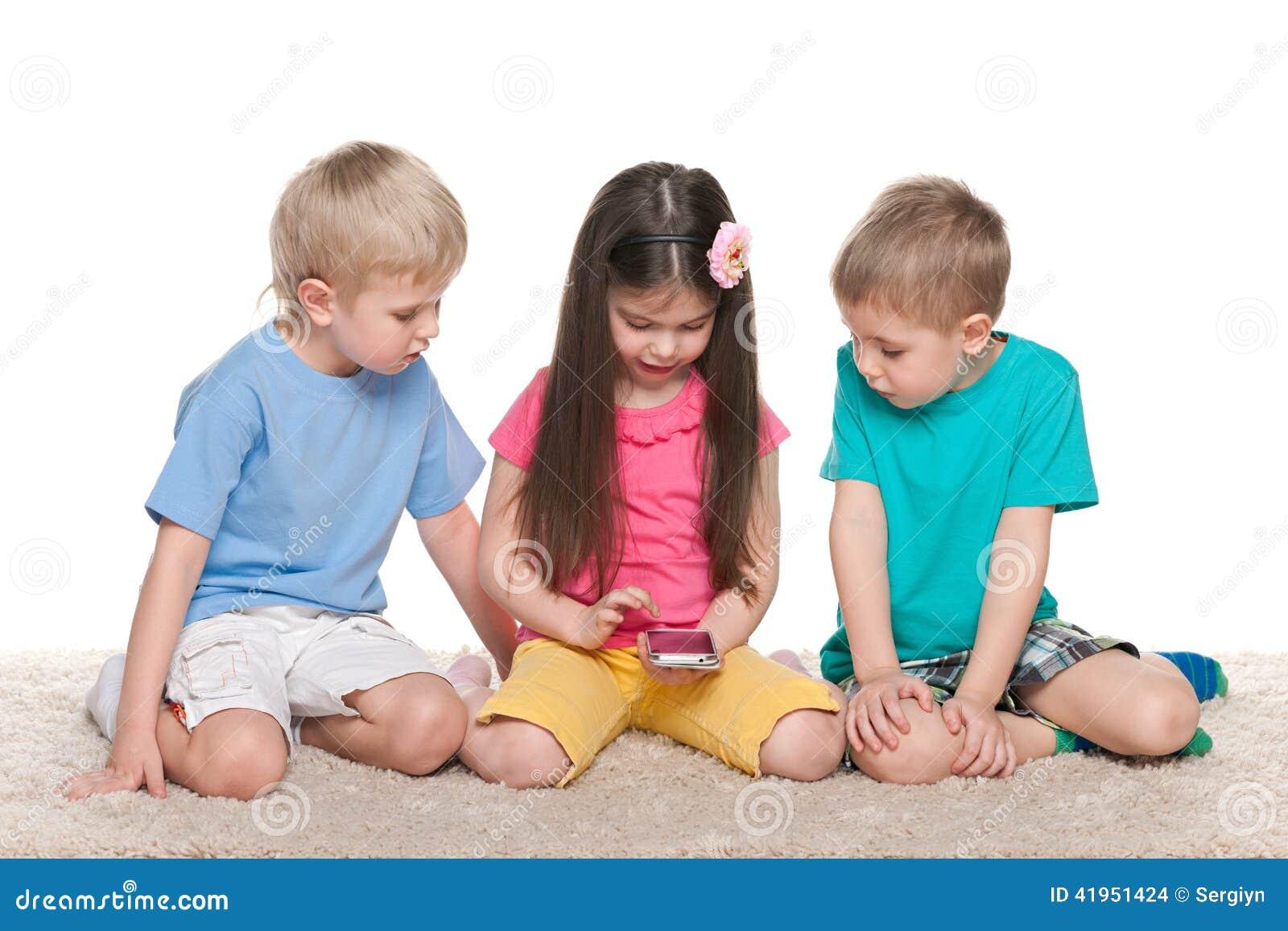 Dzieciaki z gadżetem na białym dywanie