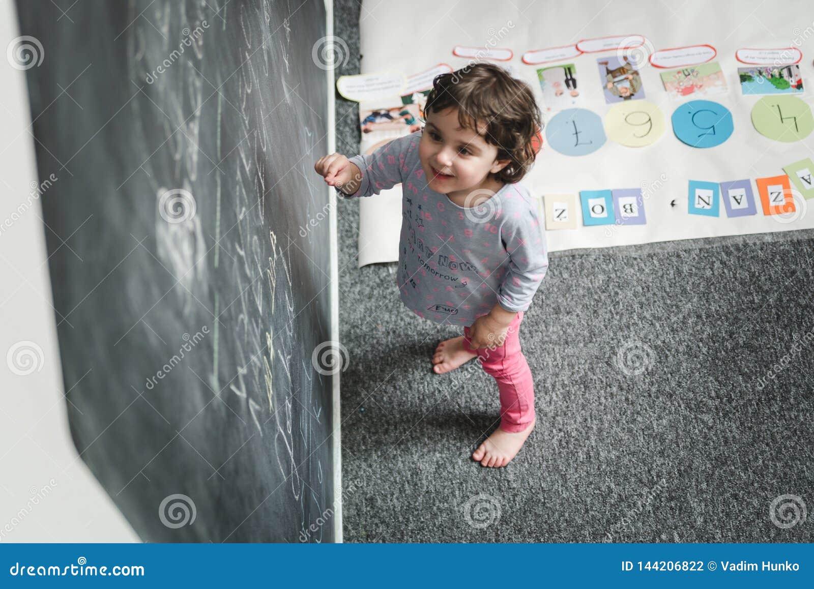 Dziecina poj?cie Szcz??liwy preschool dziewczyna rysunek na blackboard i mie? zabawie