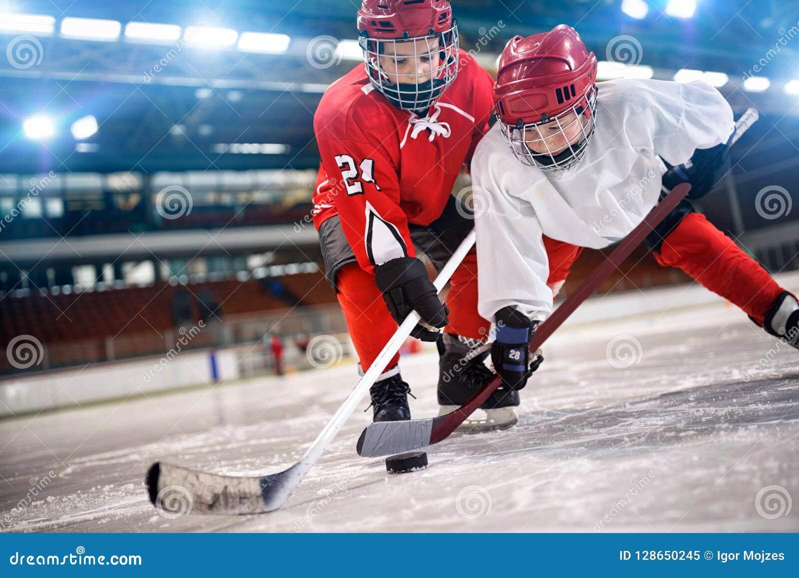 Dziecka gracz w hokeja obchodzi się krążek hokojowego na lodzie